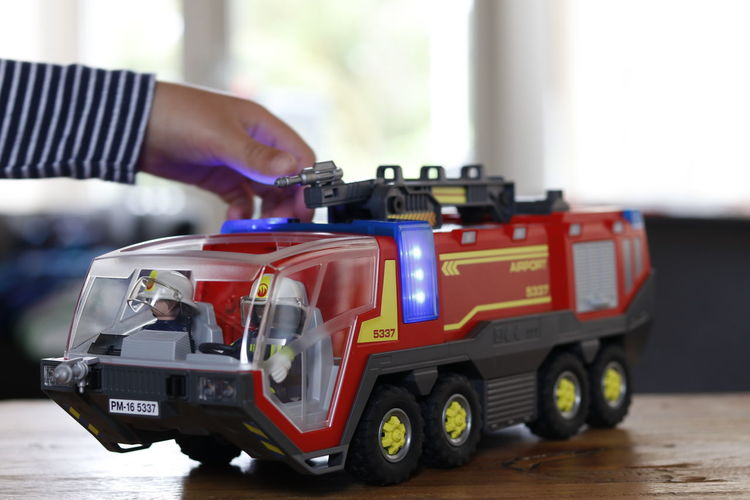 Cropped hand of child playing with toy fire engine at table