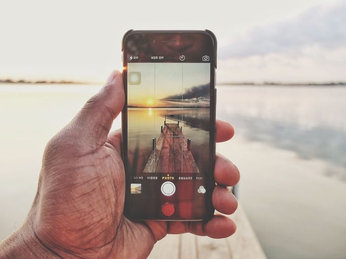 Cropped image of man photographing through smart phone