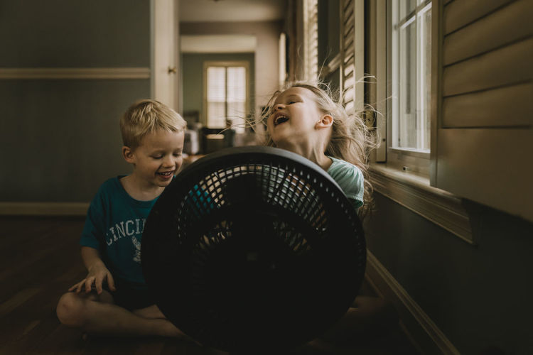 Children sitting in front of fan