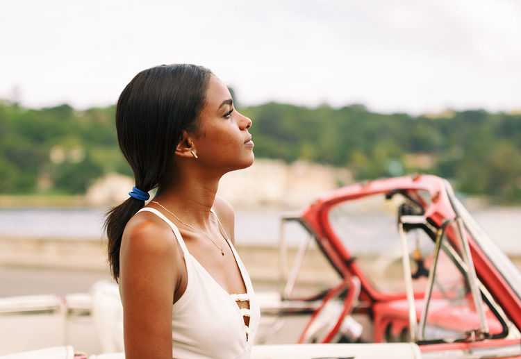 Contemplating young woman looking away while standing against boat