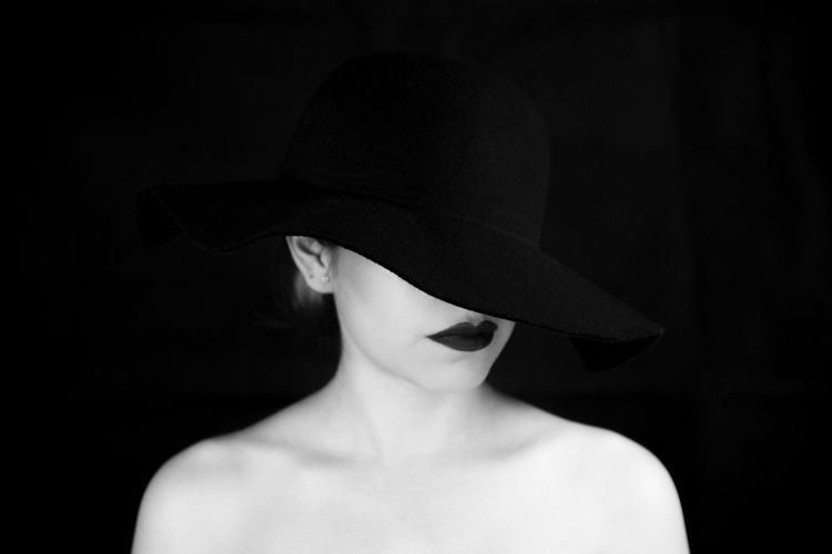 Shirtless woman wearing hat and lipstick against black background