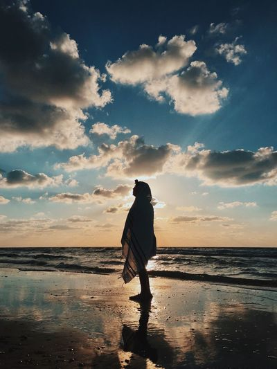 Silhouette person wrapped in blanket standing at beach during sunset