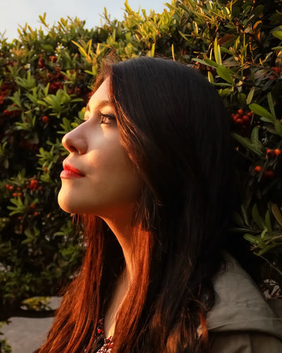 Close-up of woman looking away against plants