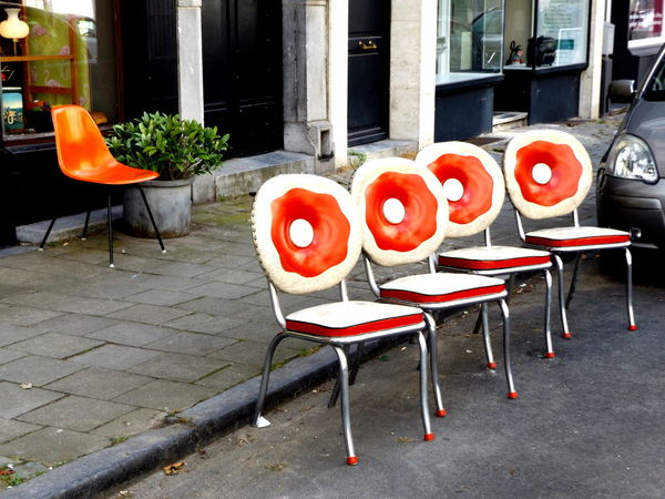 Front Row. Chair In A Row Outdoors 70's Style Vintage Streetphotography Day Low Angle View Design Multi Colored Geometric Shape City Orange Color Outside Sidewalk Town Square Vibrant Color