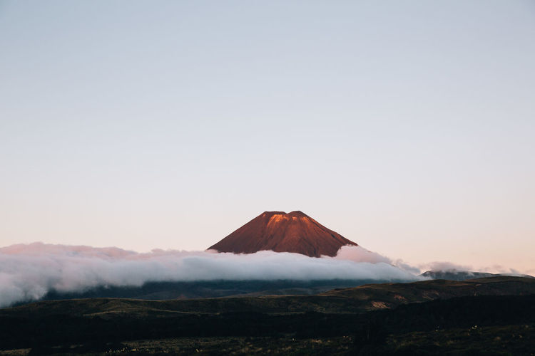 Scenic view of volcanic landscape against clear sky during sunset