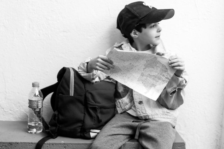 Boy holding map while sitting on table against wall