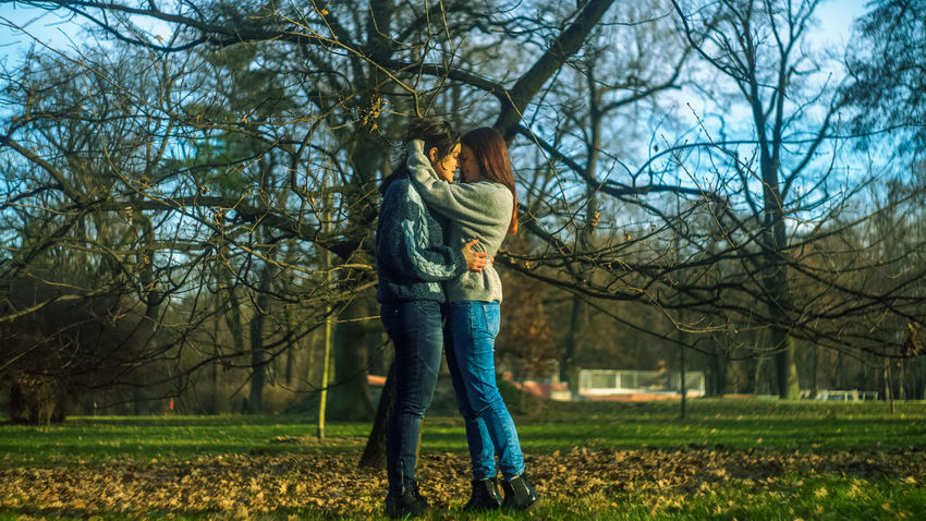 Adult Adults Only Bare Tree Branch Casual Clothing Day Full Length Grass Lesbian Lgbt Nature One Person One Young Woman Only Only Women Outdoors Park - Man Made Space People Real People Sky Standing Sunlight Tree Young Adult Young Women