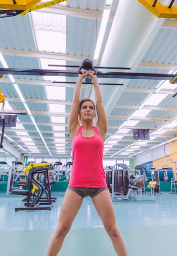 Woman Doing Exercise With Kettlebell At Gym