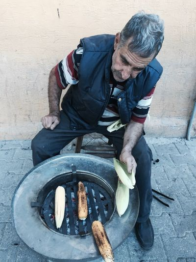 High Angle View Of Man Grilling Corns At Street