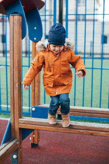 Full length of boy standing on slide at playground