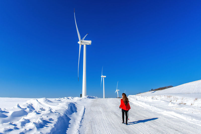 Full Length Of Woman Walking On Snow Covered Road Against Wind Turbines And Clear Blue Sky