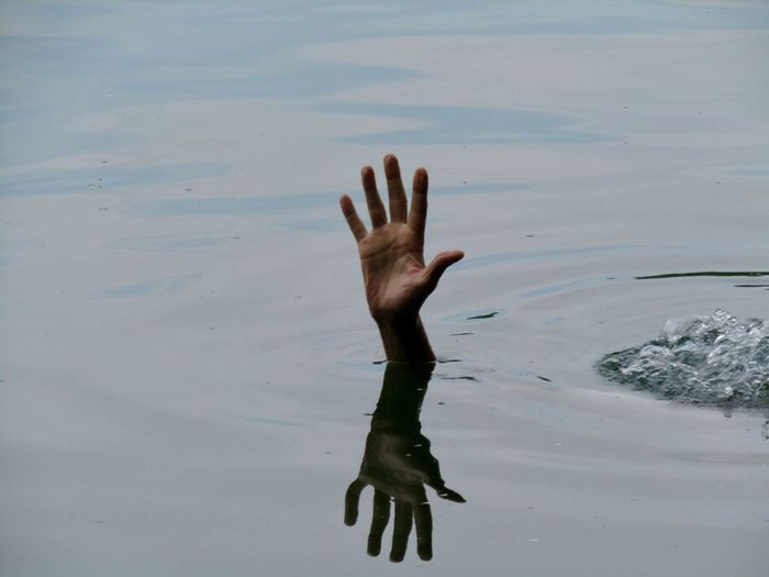 Close-up of hand drowning in sea