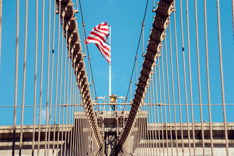Low angle view of suspension bridge against blue sky with american flag