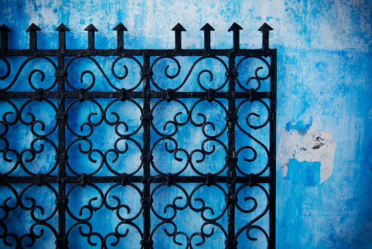 Close-up of metal gate against blue wall