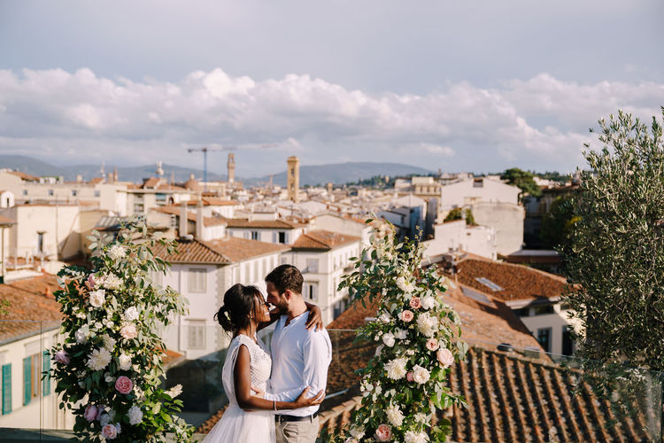 Newlywed couple embracing against cityscape