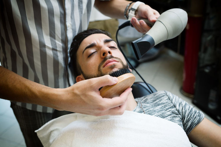 Midsection of barber combing man beard