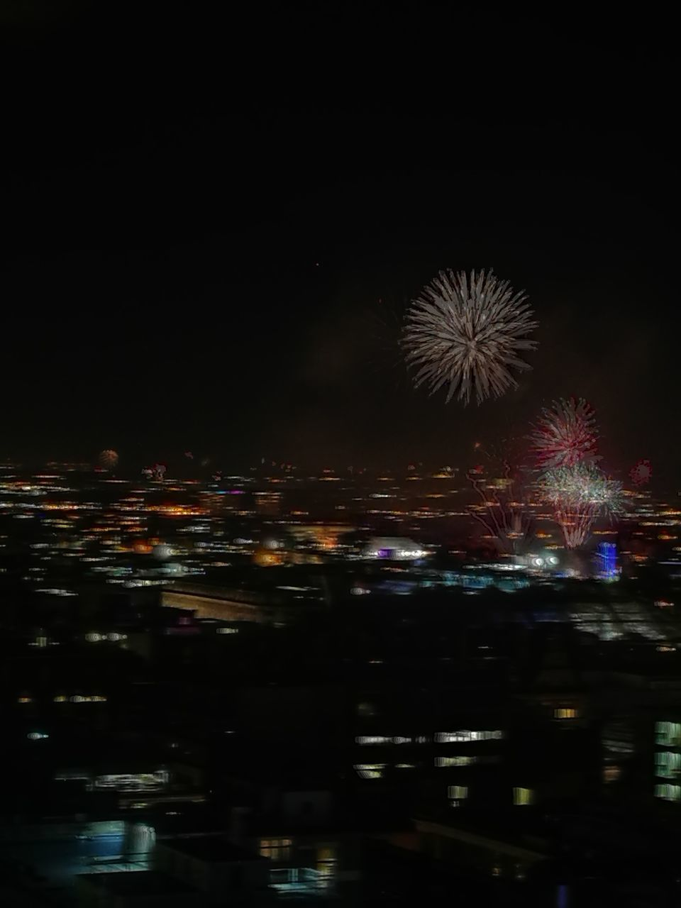 night, firework display, firework - man made object, exploding, celebration, illuminated, arts culture and entertainment, event, long exposure, motion, sky, no people, outdoors, firework, cityscape, building exterior, city