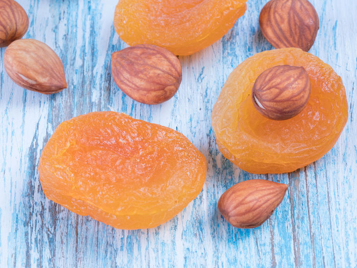 Heap of dried apricots and kernel on wooden background Apricots Close-up Day Food Food And Drink Freshness Fruit Healthy Eating High Angle View Indoors  No People Orange Color Ready-to-eat Studio Shot Sweet Food Wood - Material