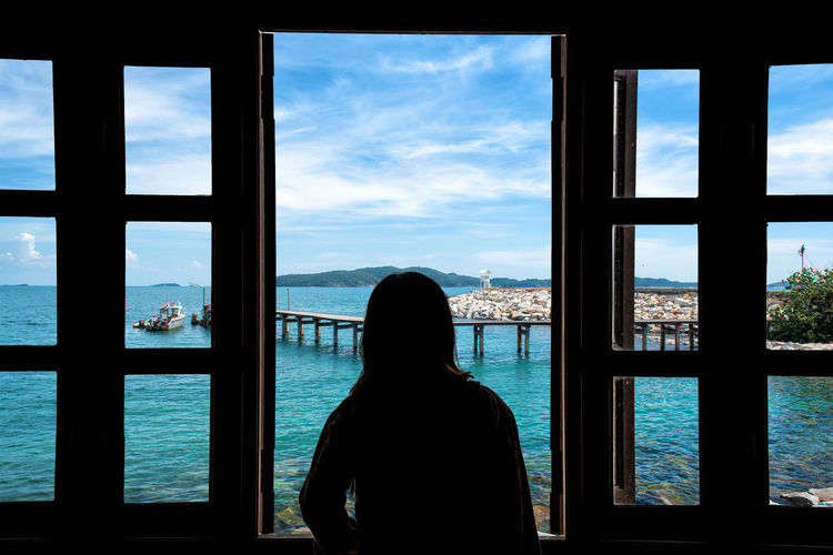 Rear view of woman looking at sea seen through window