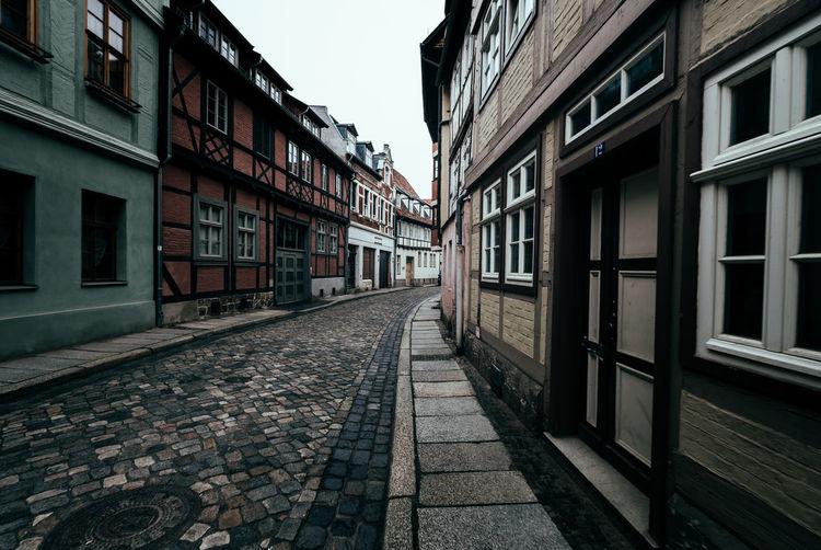 Empty walkway amidst residential buildings