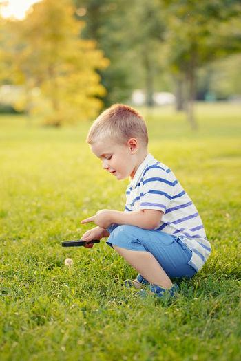 Boy crouching on field