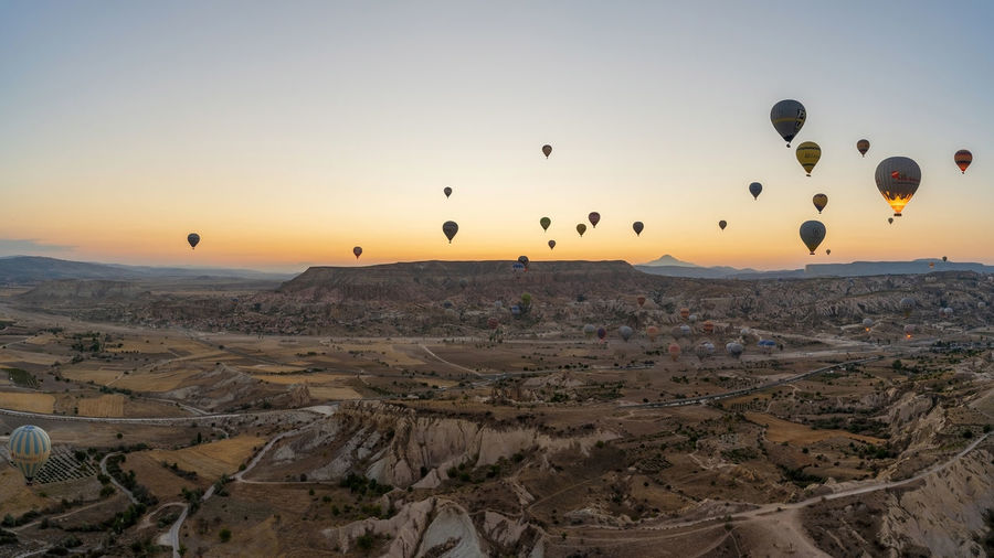 View of hot air balloons flying over landscape