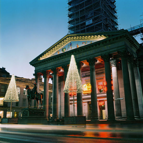 Glasgow's Gallery of Modern Art is decorated for the Christmas holidays as it undergoes renovation. Architectural Column Architecture Art Museum Blue Hour Building Exterior Built Structure Christmas Christmas Lights City Duke Of Wellington Statue Gallery Of Modern Art Glasgow  Illuminated Light Trails Long Exposure Neighborhood Map Outdoors Queen Street Renovation Royal Exchange Square Sky Statue Sunset Travel Travel Destinations