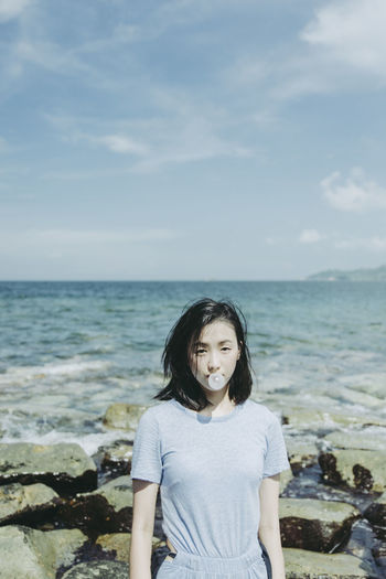 Portrait of young woman blowing bubble gum at beach against sky