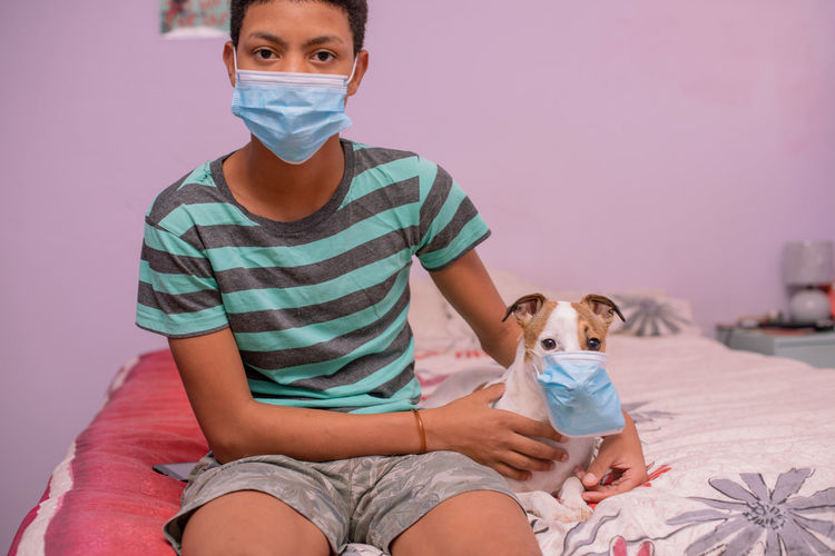 Close up portrait of teenager and his pet wearing mask