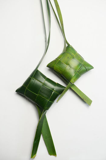 casing of ketupat on white background.ketupat is a popular traditional food from malaysia during eid al fitr festive Eid Mubarak Festive Season ASIANNFOOD Aidilfitri Casing White Background Shape Pattern Handmade Sticky Rice White Background Studio Shot Close-up Green Color Leaves
