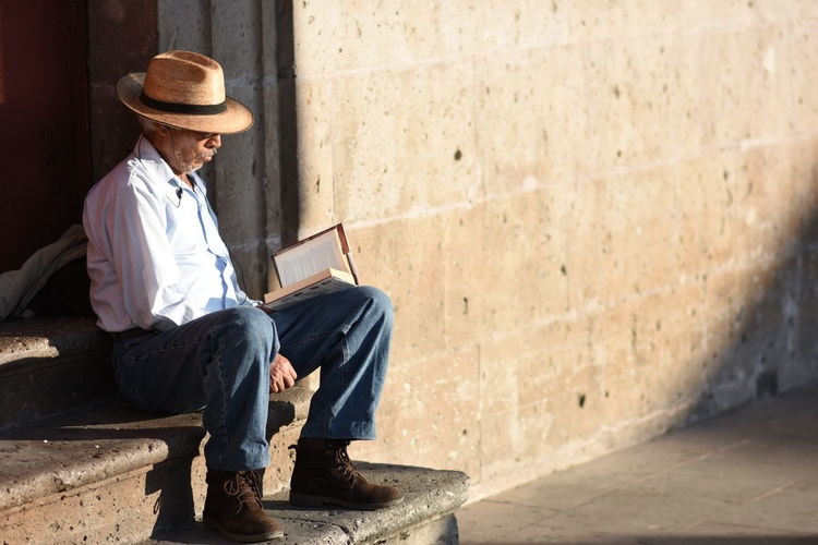 Adult Adults Only Business Chilling City Cowboy Hat Day Fedora  Golden Hour Hat Men One Man Only One Person Only Men Outdoors People Reading Senior Adult Senior Men Sitting Suit