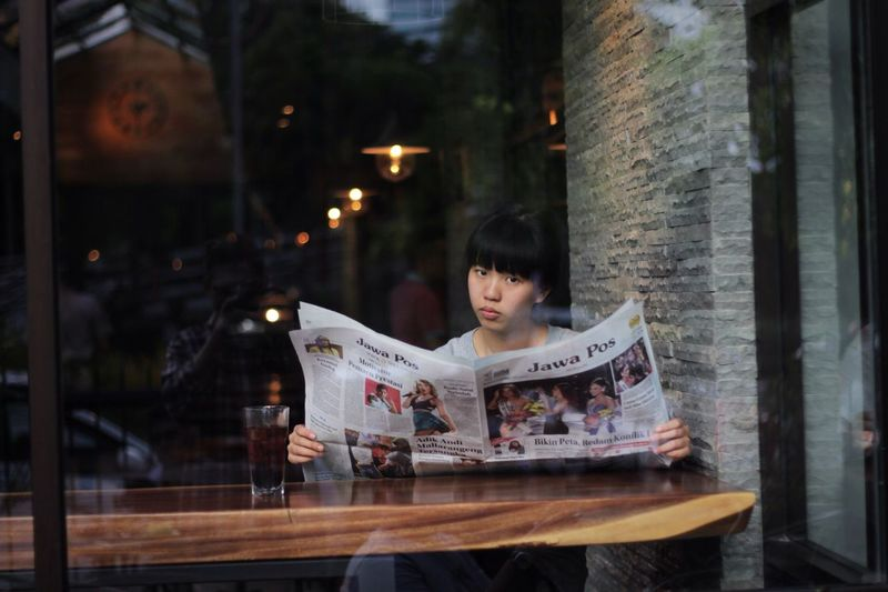 Portrait Of Woman Reading Newspaper In Cafe Seen Through Glass