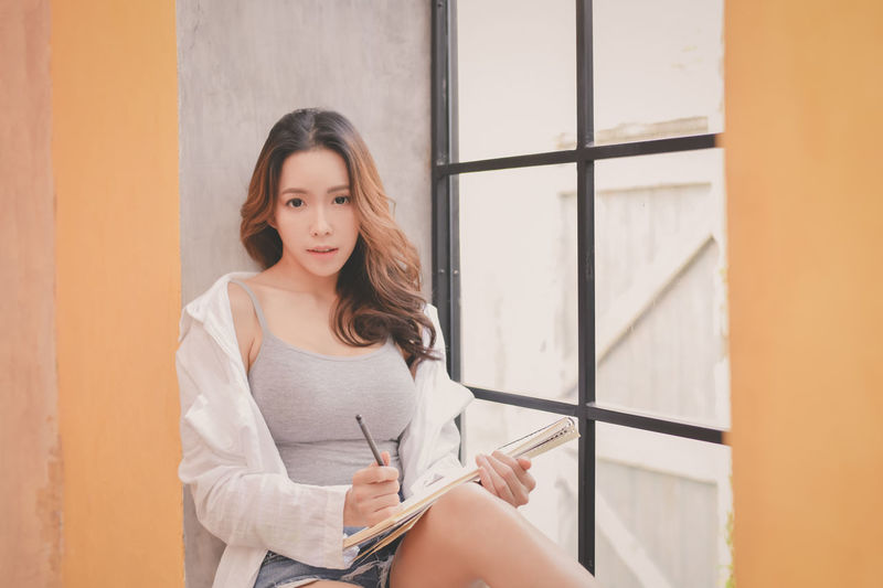 Adult Beautiful Woman Beauty Casual Clothing Front View Hair Hairstyle Holding Indoors  Lifestyles Looking At Camera One Person Portrait Real People Smiling Standing Three Quarter Length Women Young Adult Young Women