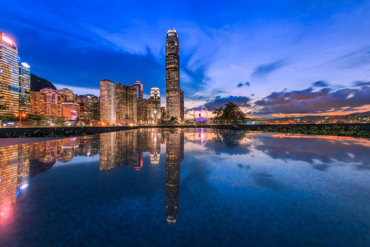 Modern office buildings in Central Hong Kong. Reflection Water Sky Architecture Building Exterior Lake Waterfront Built Structure Nature Blue Cloud - Sky Building No People Symmetry Outdoors Illuminated City Travel Destinations Tower Office Building Exterior Skyscraper Reflection Lake Landmark HongKong City