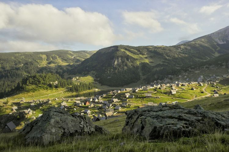 Houses on grassy field at mountain village