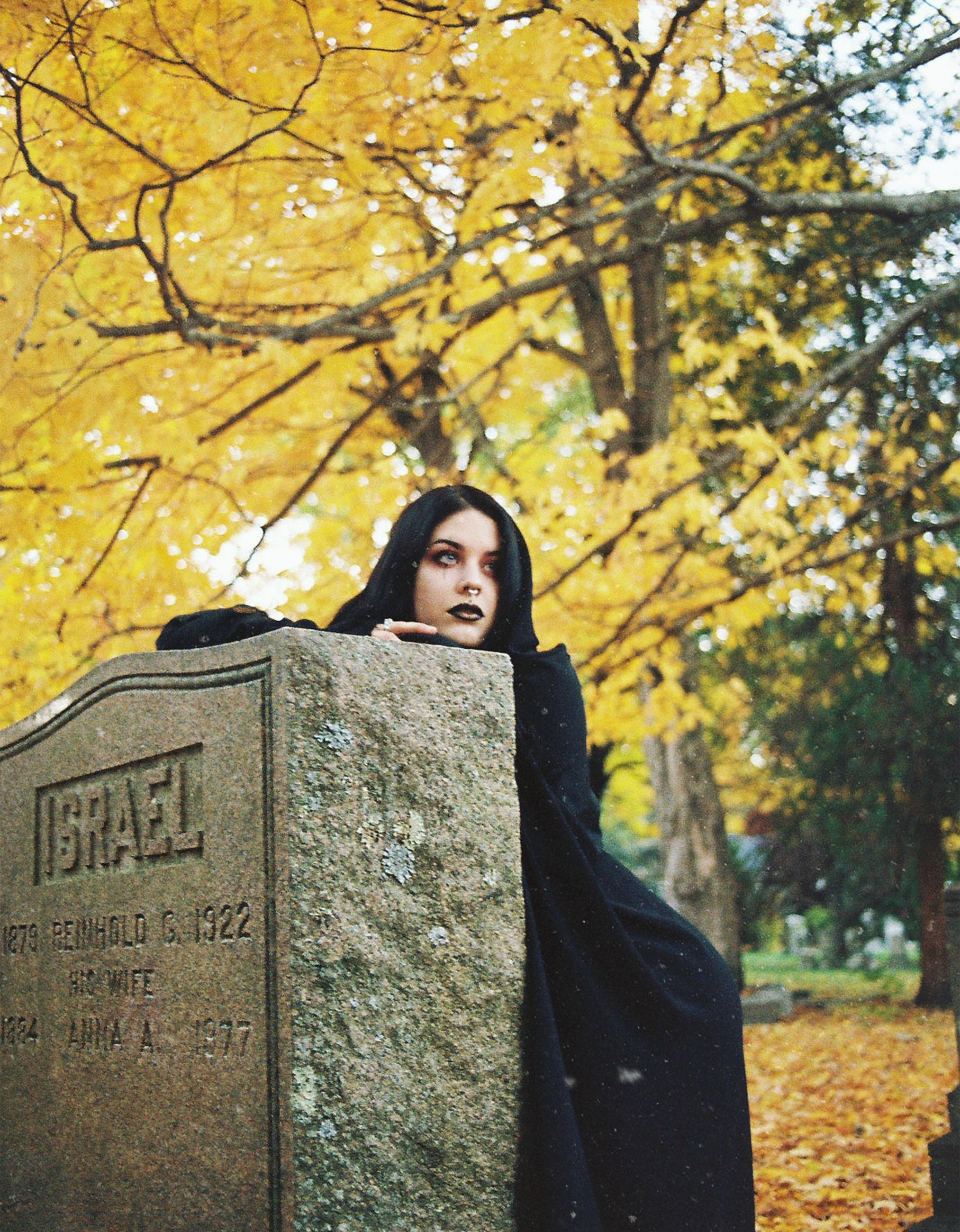 tree, autumn, cemetery, grave, one person, tombstone, plant, nature, change, day, real people, young adult, portrait, standing, emotion, stone, lifestyles, outdoors