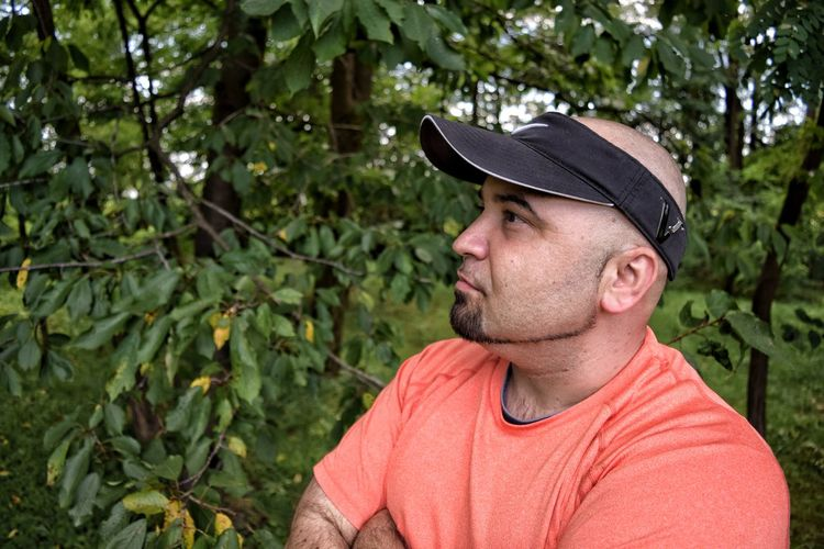 Romanian man looks into distance amongst trees - profile view EyeEm Selects Produce Selection Fruit Picking Romanian  Orchard Decisions Poses Arms Folded Man In Front Of Trees Profile View Orange Shirt