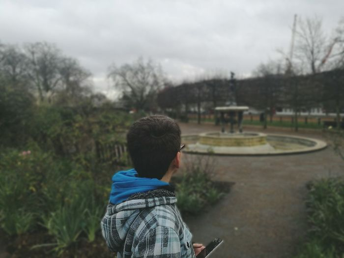 Boy Holding Mobile Phone In Park Against Cloudy Sky
