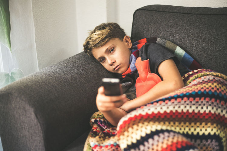 Boy resting on sofa with blanket while watching television at home