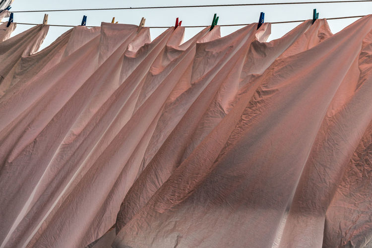 Low angle view of pink sheets hung to dry in a breeze on clothesline