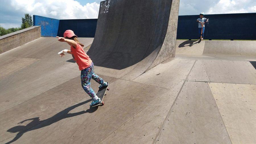 Siblings skateboarding in park