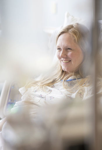 A pregnant woman waits for labor to begin while sitting in a hospital bed. Hair Women Portrait Happiness Smiling Hospital Beautiful Woman Emotion Headshot Indoors  Hairstyle Cheerful Blond Hair Enjoyment Pregnancy Medical Adult Patient Labor Front View Lifestyles Selective Focus One Person Casual Clothing Healthcare And Medicine Beautiful