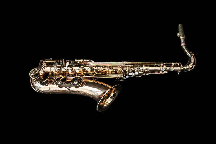 A golden saxophone. Jazz Sax Shiny Arts Culture And Entertainment Black Background Brass Brass Instrument  Gold Colored Jazz Music Lying Down Metal Music Musical Instrument No People Saxophone Side View Single Object Studio Shot Wind Instrument