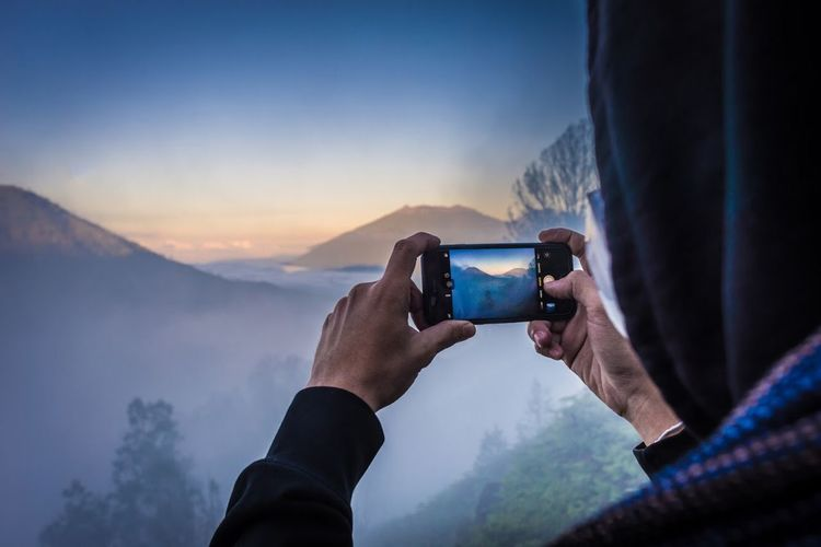 Midsection of man using mobile phone against mountains