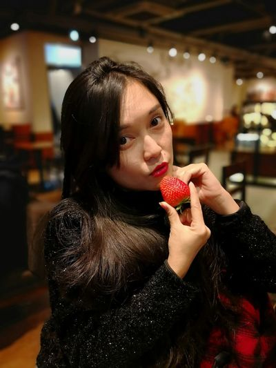 Portrait of beautiful woman eating strawberry while sitting at restaurant