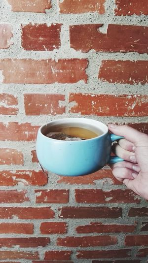Cropped hand holding tea against brick wall