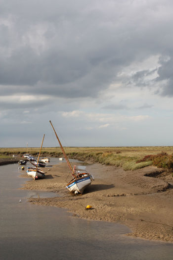 Two sailing boats on the beach at low tide in Blakeney, Norfolk, United Kingdom Sky Cloud - Sky Land Transportation Day Nature Mode Of Transportation Nautical Vessel Sand Water Beauty In Nature Beach No People Tranquility Scenics - Nature Tranquil Scene Horizon Outdoors Non-urban Scene Low Tide Copy Space