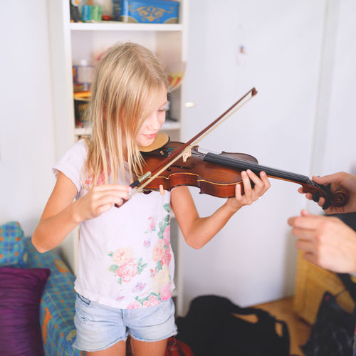 Young blond girl, primary school age, playing the violin, having violin lesson Arts Culture And Entertainment Blond Hair Child Childhood Hair Hairstyle Indoors  Music Musical Instrument Playing Practicing Primary School Age Skill  Violin Violin Lesson Violinist Wooden String Instrument Young Girl