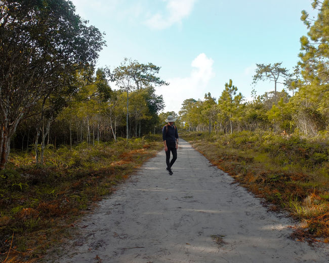 Young man standing on footpath amidst trees