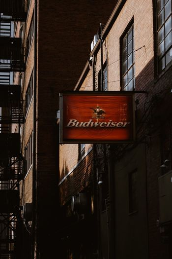 Budweiser Budwiser Building Exterior Built Structure Architecture No People Communication Building Day Wall Brick Wall Outdoors Information Sign City Residential District Hanging Low Angle View Text Sunlight Nature Fire Escape